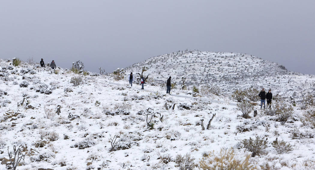 People walk to a viewpoint at Red Rock Canyon Overlook in the snow on Thursday, Dec. 26, 2019, ...