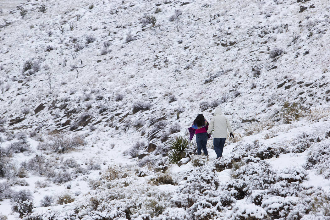 People walk through the snow at Red Rock Canyon Overlook on Thursday, Dec. 26, 2019, in Las Veg ...