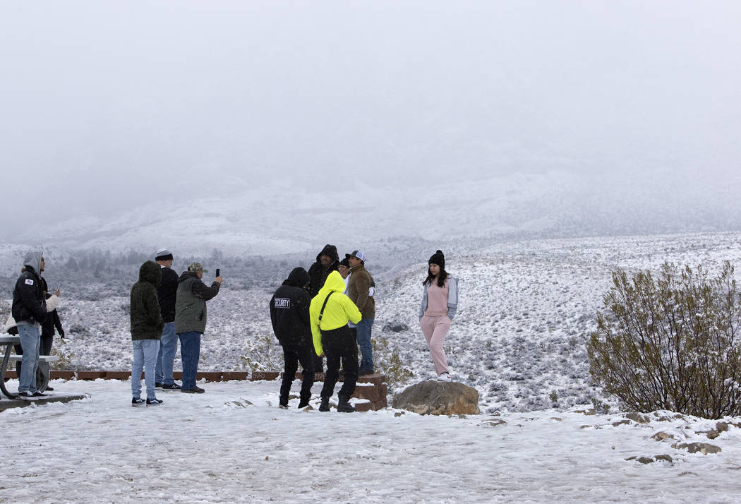 People pose for photos in the snow at Red Rock Canyon Overlook on Thursday, Dec. 26, 2019, in L ...