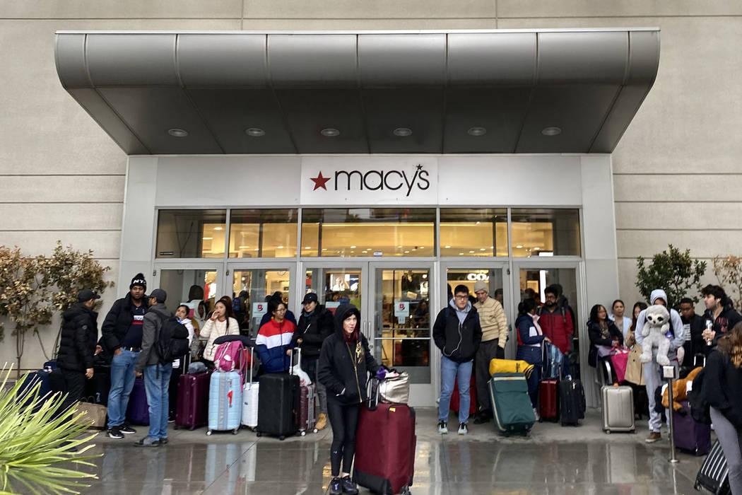 People shelter from the rain at the door to Macy's at Fashion Show mall in Las Vegas as they wa ...