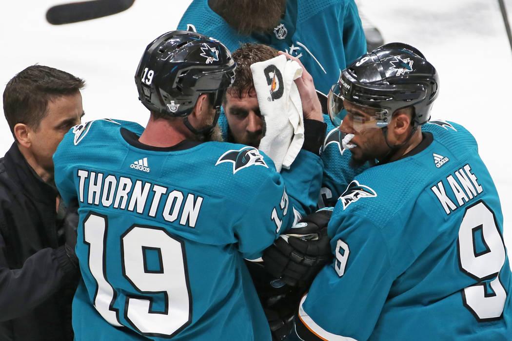 Sharks center Joe Pavelski, middle, is helped off the ice by Sharks left wing Evander Kane (9) ...