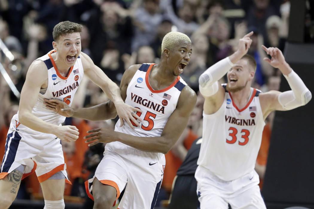 Virginia's Mamadi Diakite, center, reacts with teammates Kyle Guy and Jack Salt (33) after hitt ...