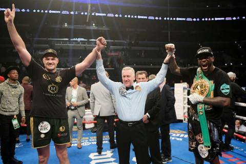 Tyson Fury, left, of England, poses with Deontay Wilder, right, along with referee Jack Reiss a ...