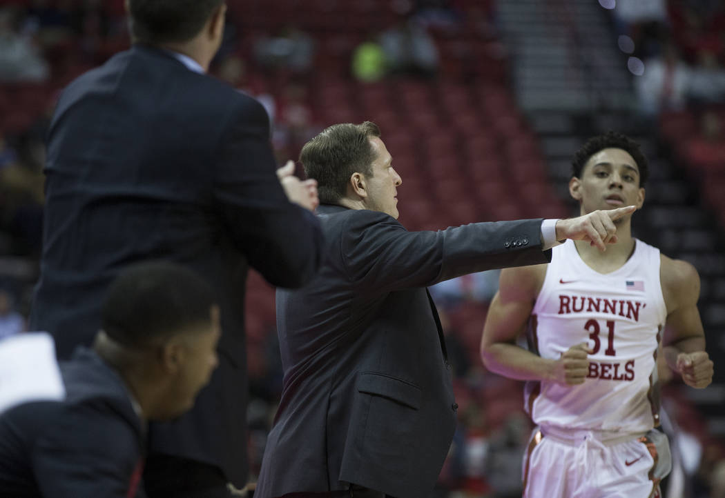 UNLV Rebels head coach T.J. Otzelberger, middle, gives direction to UNLV Rebels guard Marvin Co ...