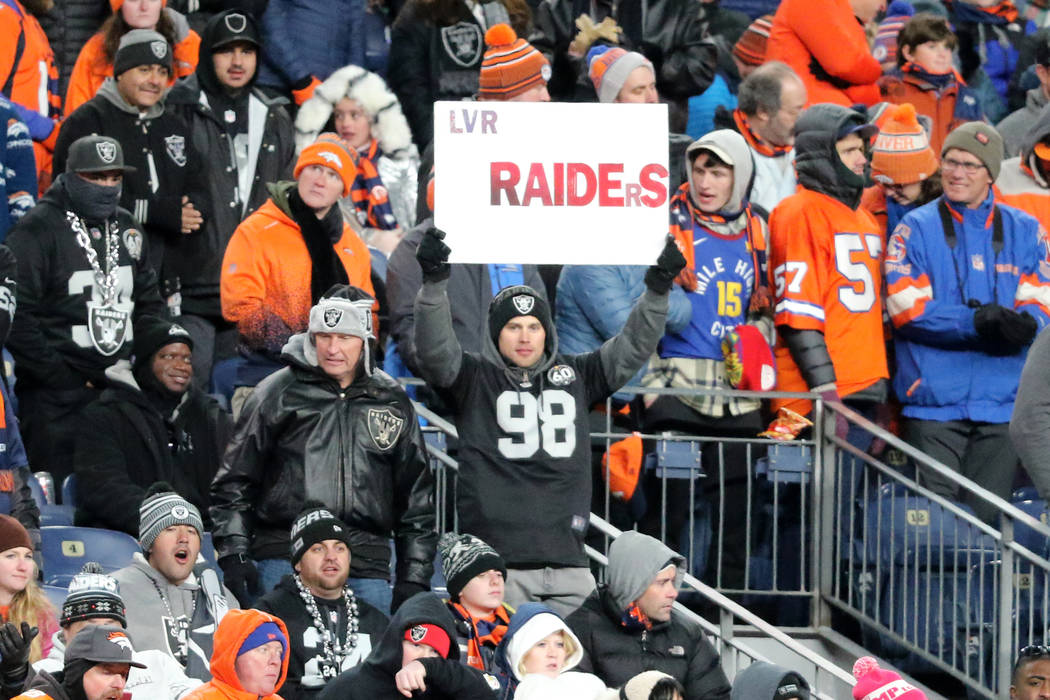 An Oakland Raiders fan holds up a sign during the second half of an NFL game against the Denver ...