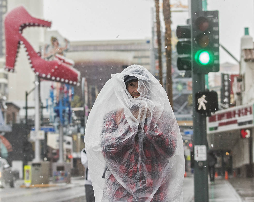 Bruce Outwater tries to stay dry while waking on Fremont Street in the early morning snow in Do ...