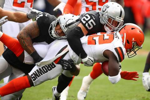 Cleveland Browns' Jabrill Peppers, right, is tackled by Oakland Raiders' Erik Harris (25) and K ...