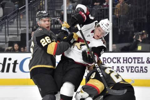 Arizona Coyotes center Christian Dvorak (18) battles between Vegas Golden Knights center Paul S ...