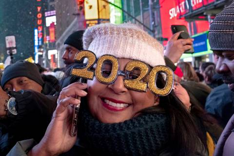 People celebrate the New Year on Times Square in New York, Wednesday, Jan. 1, 2020, (AP Photo/C ...