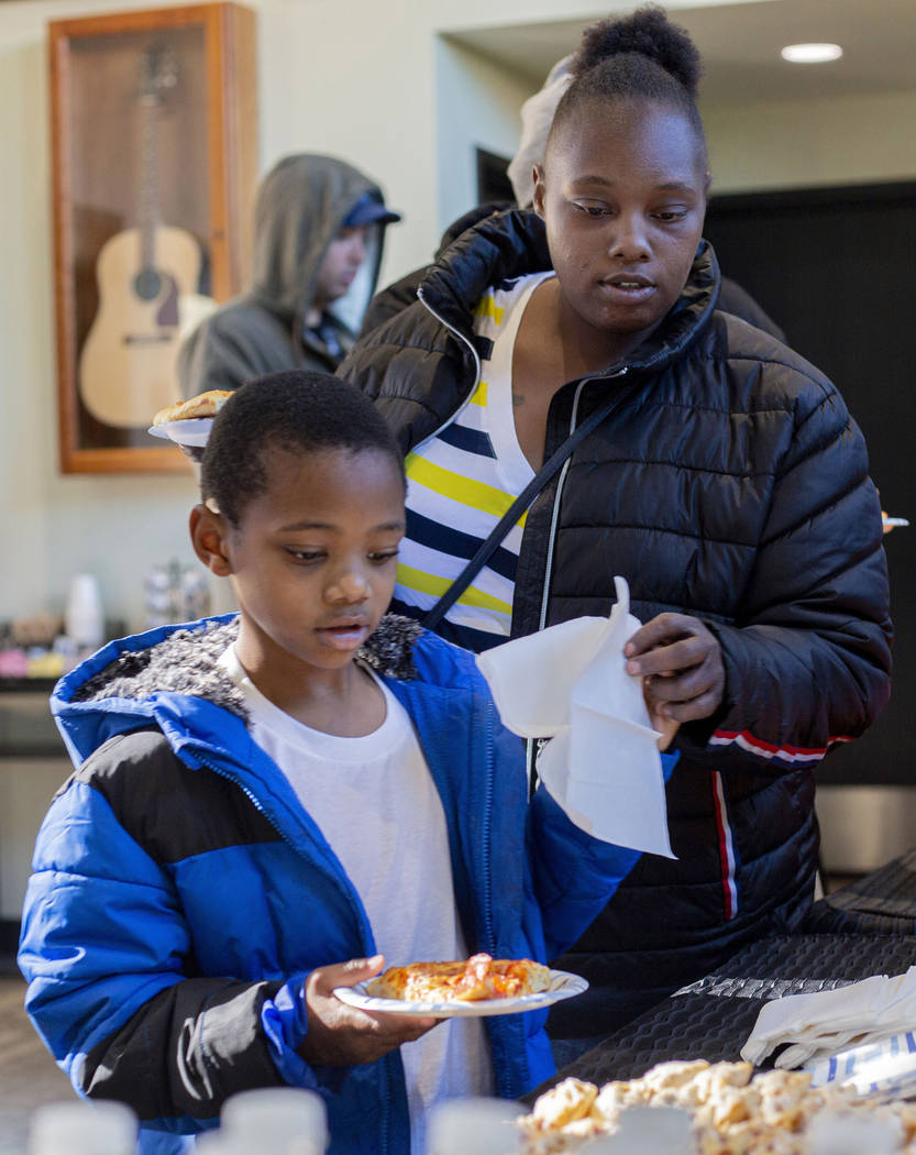 Andru Roach, 7, and Dayshena Thomas receive a meal during a luncheon for the tenants of the Alp ...