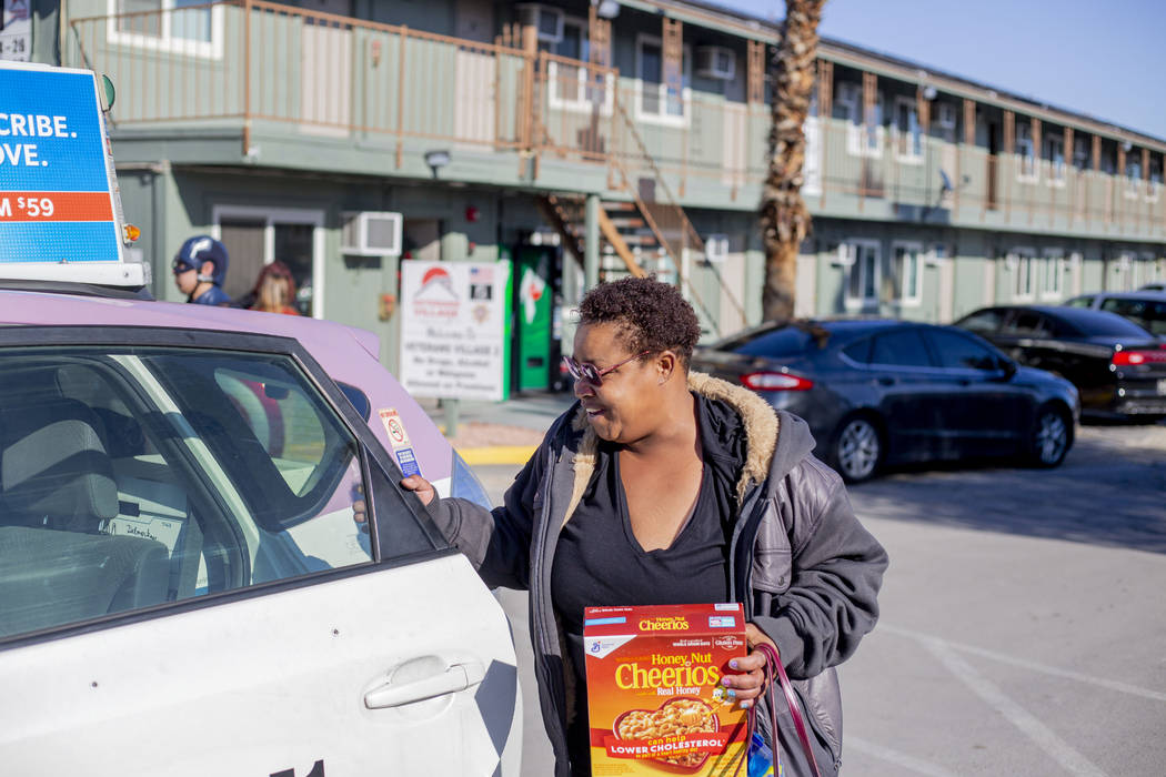 Alpine Motel tenant Tia Dotson gets into a complimentary taxi after a care package giveaway at ...