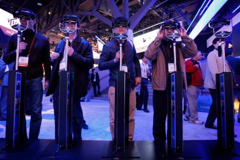 Showgoers try out 3D glasses at the Panasonic booth during the 2010 Consumer Electronics Show. ...