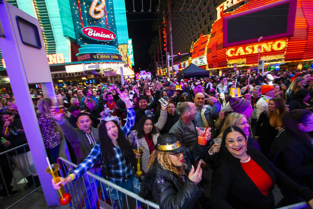 New Year's Eve revelers dance by a stage at the Fremont Street Experience in downtown Las Vegas ...