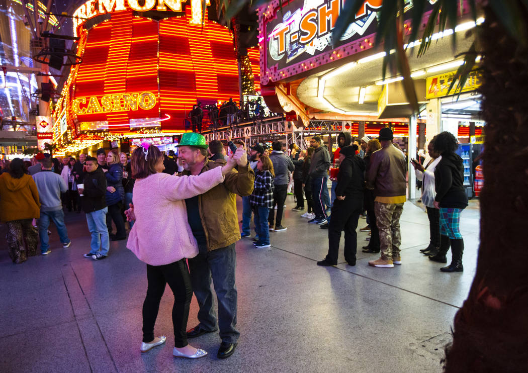 Sherry Schneider, left, of South Carolina, dances with Rob Schneider as New Year's Eve revelers ...