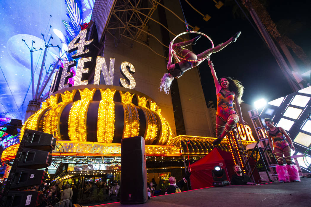 Aerialists perform on stage as New Year's Eve revelers gather at the Fremont Street Experience ...
