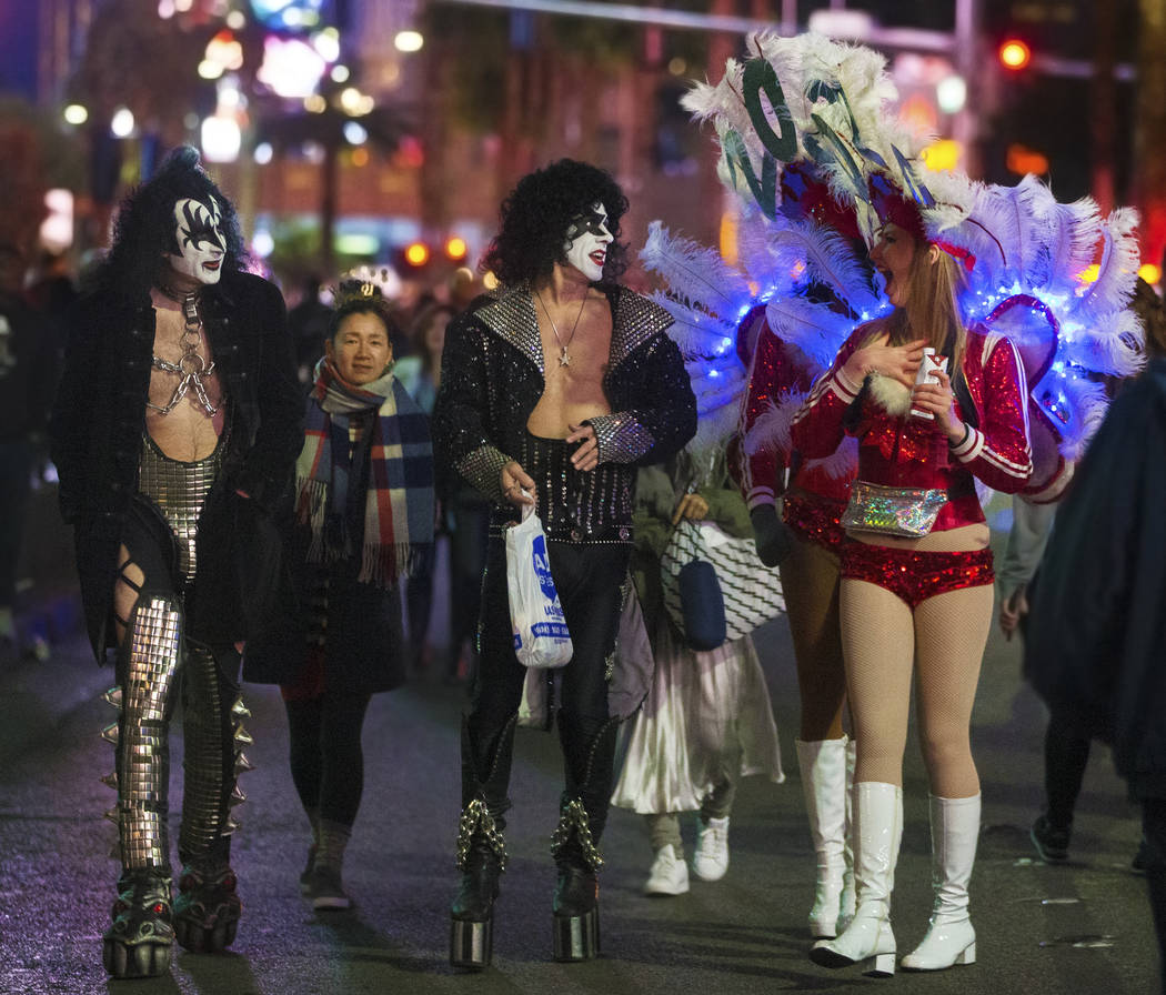 Show girls, right, share a moment with street performers dressed in Kiss attire on the Strip on ...