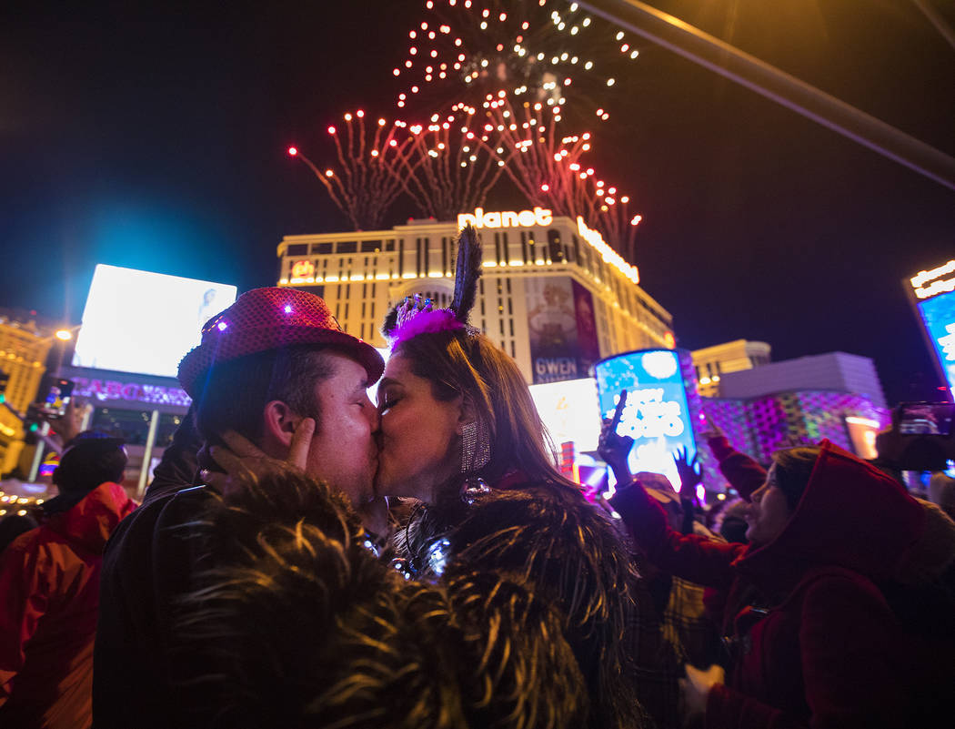 Moses Carpio, of Las Vegas, kisses his girlfriend Teresa Enriquez, of Juarez, on New Year&#x201 ...