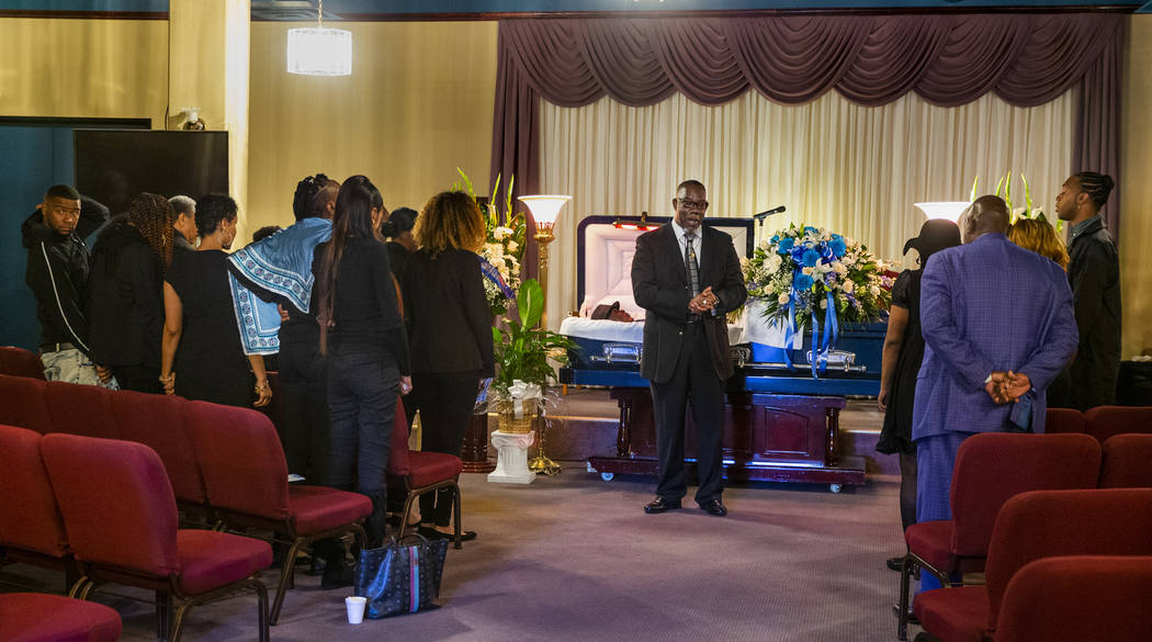 Bishop Tyrone L. Seals leads attendees in prayer for Don Bennett, a maintenance man and hero of ...