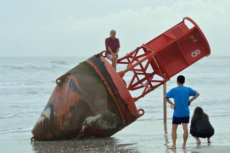 Beachgoers inspect a navigational marker that washed up on the beach last week in New Smyrna Be ...