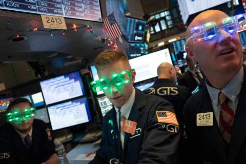 Stock traders wear New Year's 2020 party glasses at the New York Stock Exchange, Tuesday, Dec. ...