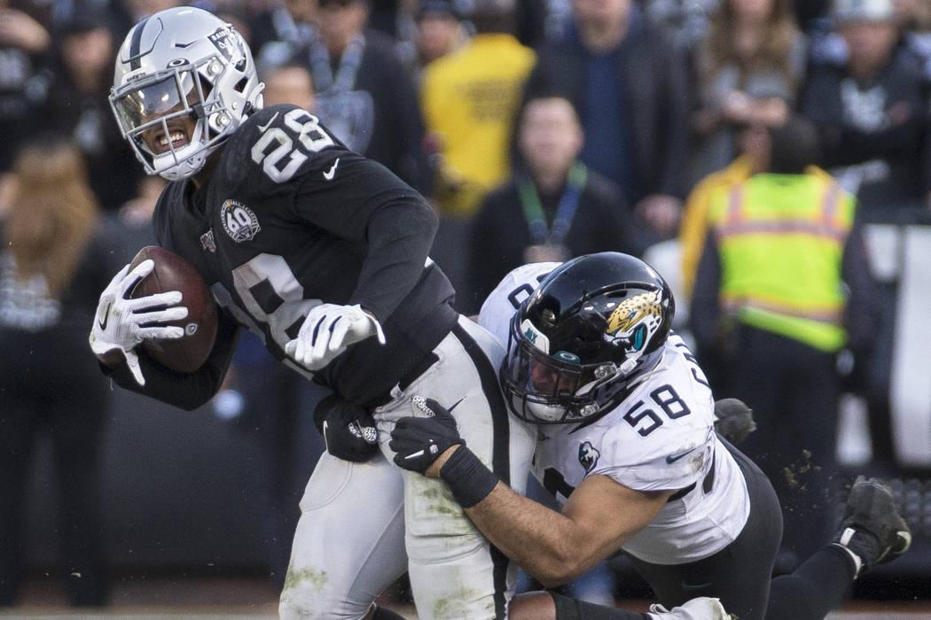 Oakland Raiders running back Josh Jacobs (28) drags Jacksonville Jaguars outside linebacker Aus ...