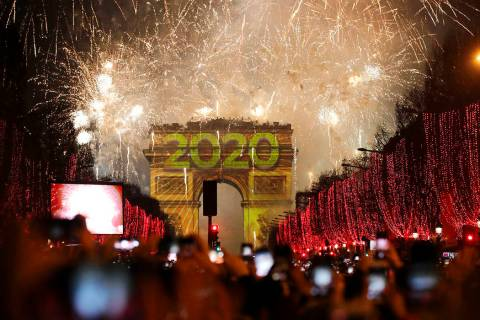 Revellers photograph fireworks over the Arc de Triomphe as they celebrate the New Year on the C ...
