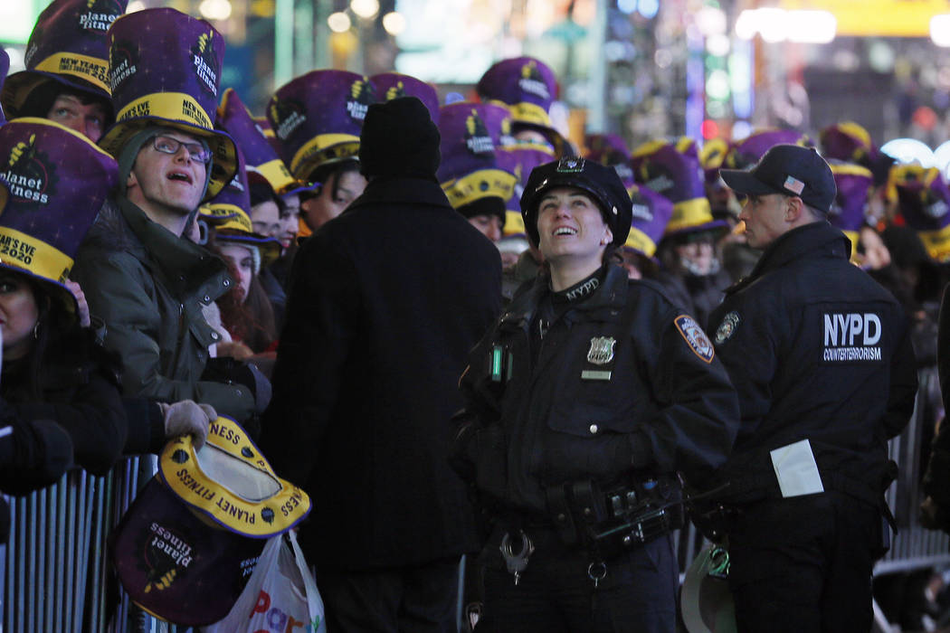 New York City police officers and revelers wait in New York's Times Square, Tuesday, Dec. 31, 2 ...