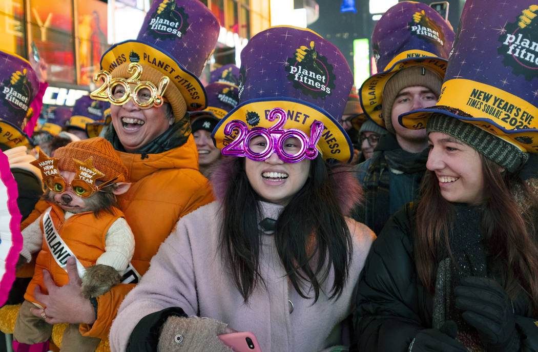 Revelers watch musical entertainment on Times Square in New York, Tuesday, Dec. 31, 2019, as pe ...