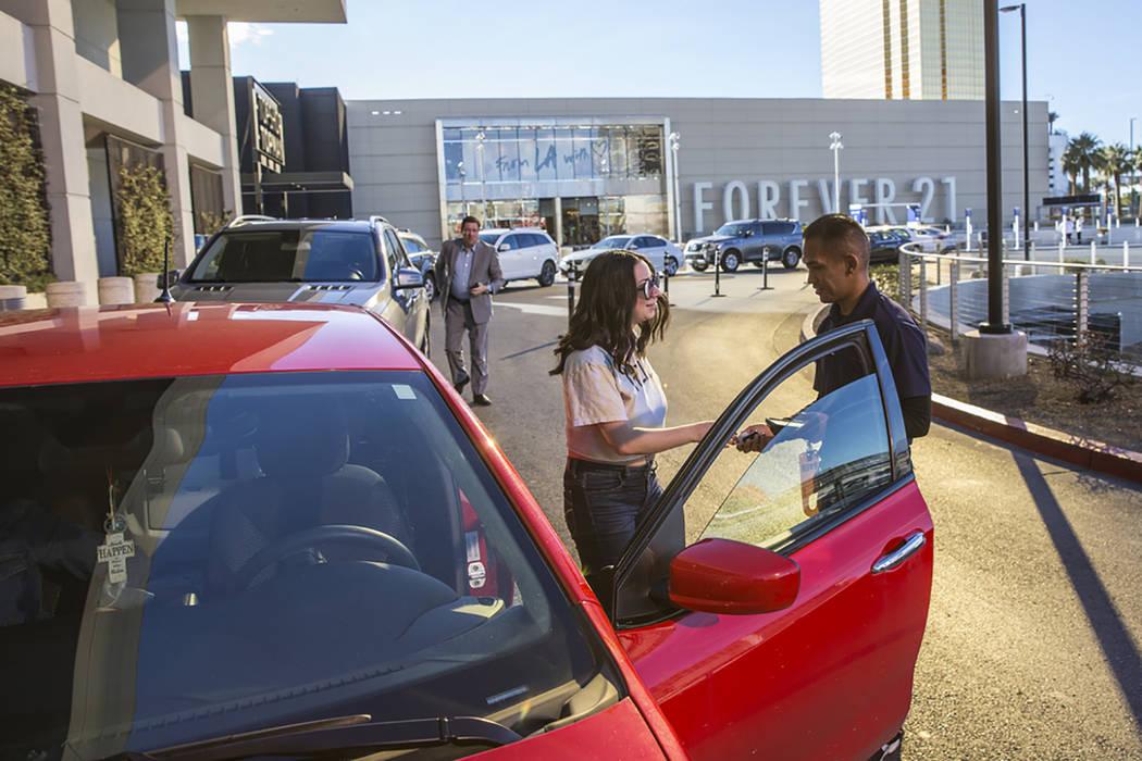 Mark Reolegio, right, valets Jennifer Sandoval's car outside The Capital Grille on Wednesday, F ...