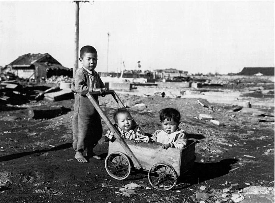 A Japanese boy pushes two younger children in a wagon in this photograph shot in Hiroshima, Jap ...