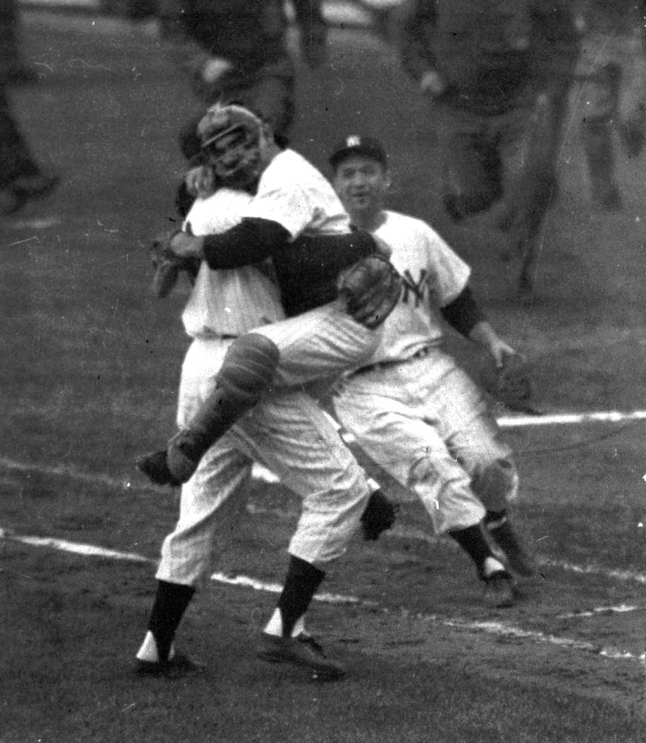 FILE- In this Oct. 8, 1956, file photo, New York Yankees catcher Yogi Berra is embraced by pitc ...