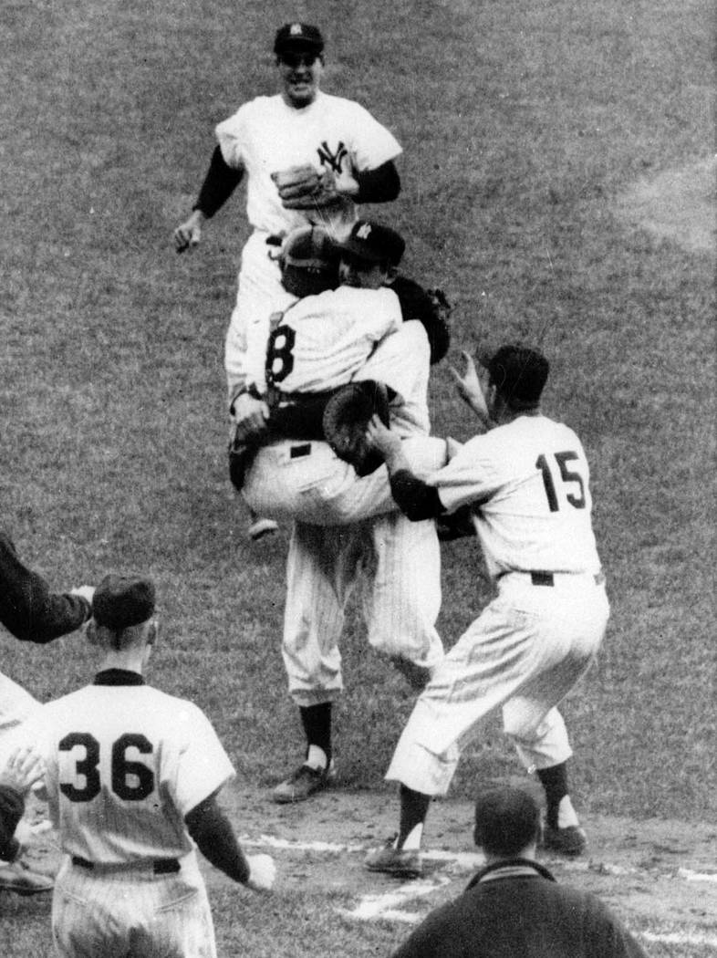 FILE - In this Oct. 8, 1956, file photo, New York Yankees catcher Yogi Berra (8) has jumped int ...