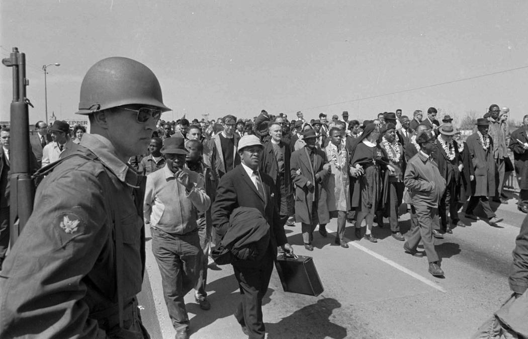 An armed soldier stands on duty at Selma Alabama, March 21, 1965 as civil rights marchers head ...