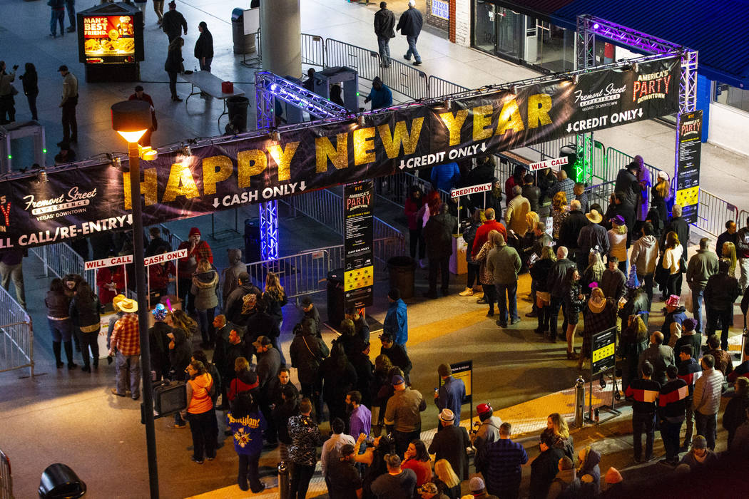 New Year's Eve revelers line up to enter the Fremont Street Experience in downtown Las Vegas on ...