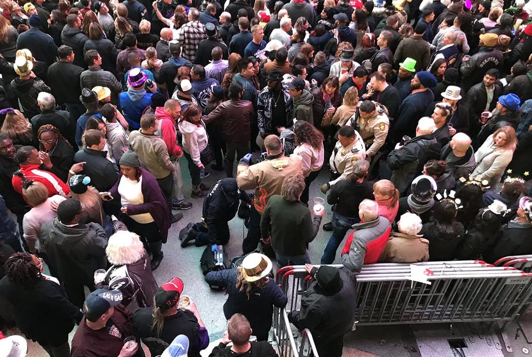 First responders assist a person who fell on Fremont Street during the New Year's Eve celebrati ...