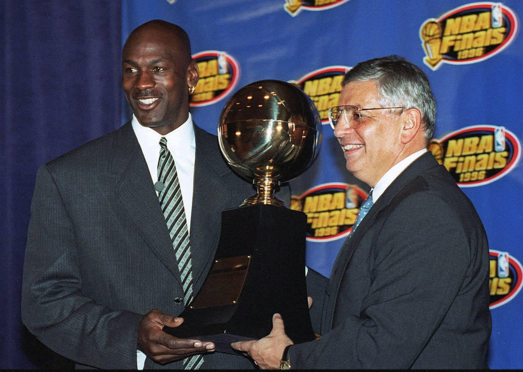 Chicago Bulls' Michael Jordan, left, receives the NBA Finals Most Valuable Player trophy from C ...