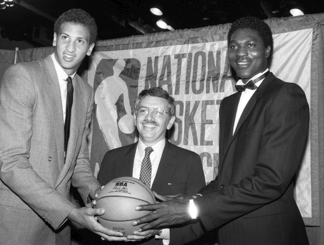 NBA commissioner David Stern, center, is flanked by Akeem Olajuwon, right, the No. 1 pick overa ...