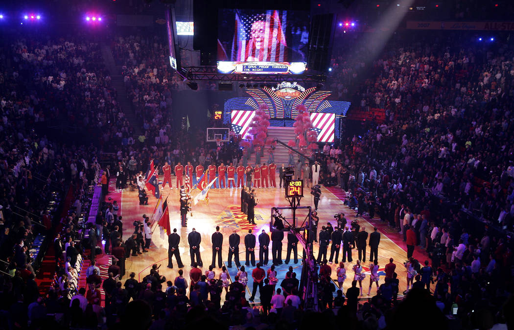 Basketball fans stand as Las Vegas headliner Danny Gans and his band sing the National Anthem b ...