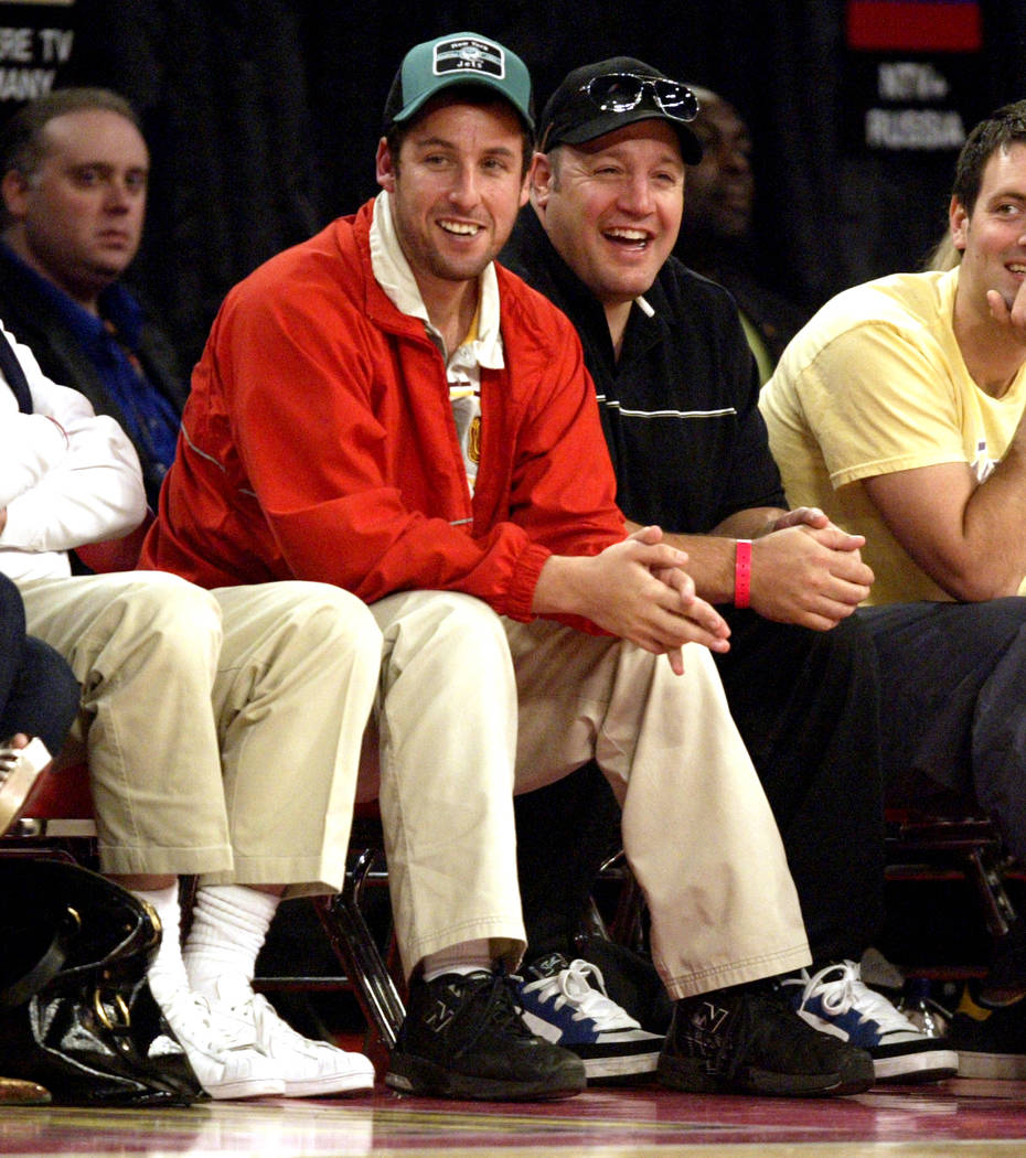 Actor Adam Sandler, left, and Kevin James laugh during the NBA All-Star basketball game at the ...