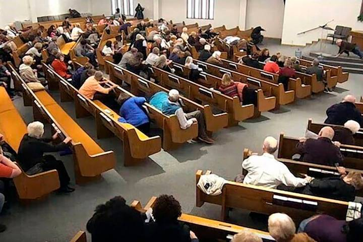 Churchgoers take cover while a congregant armed with a handgun, top left, engages a man who ope ...