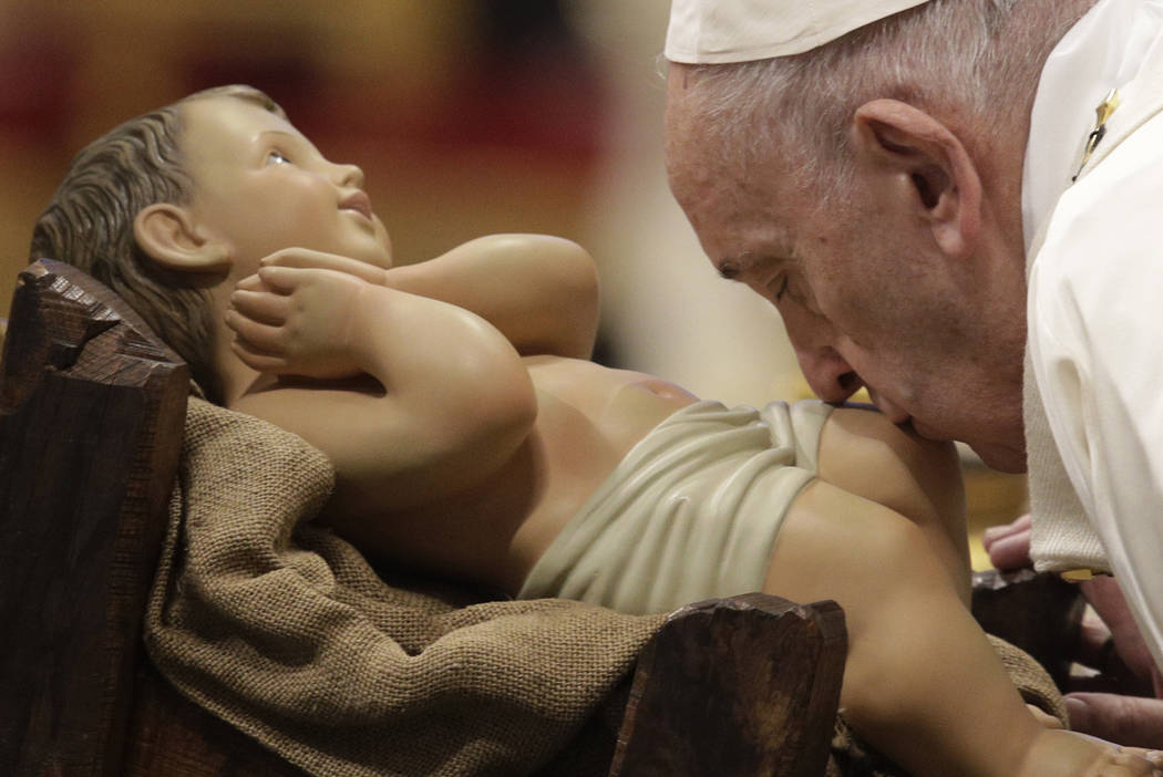 Pope Francis kisses a statue of Baby Jesus as he presides over a Mass for the solemnity of St. ...