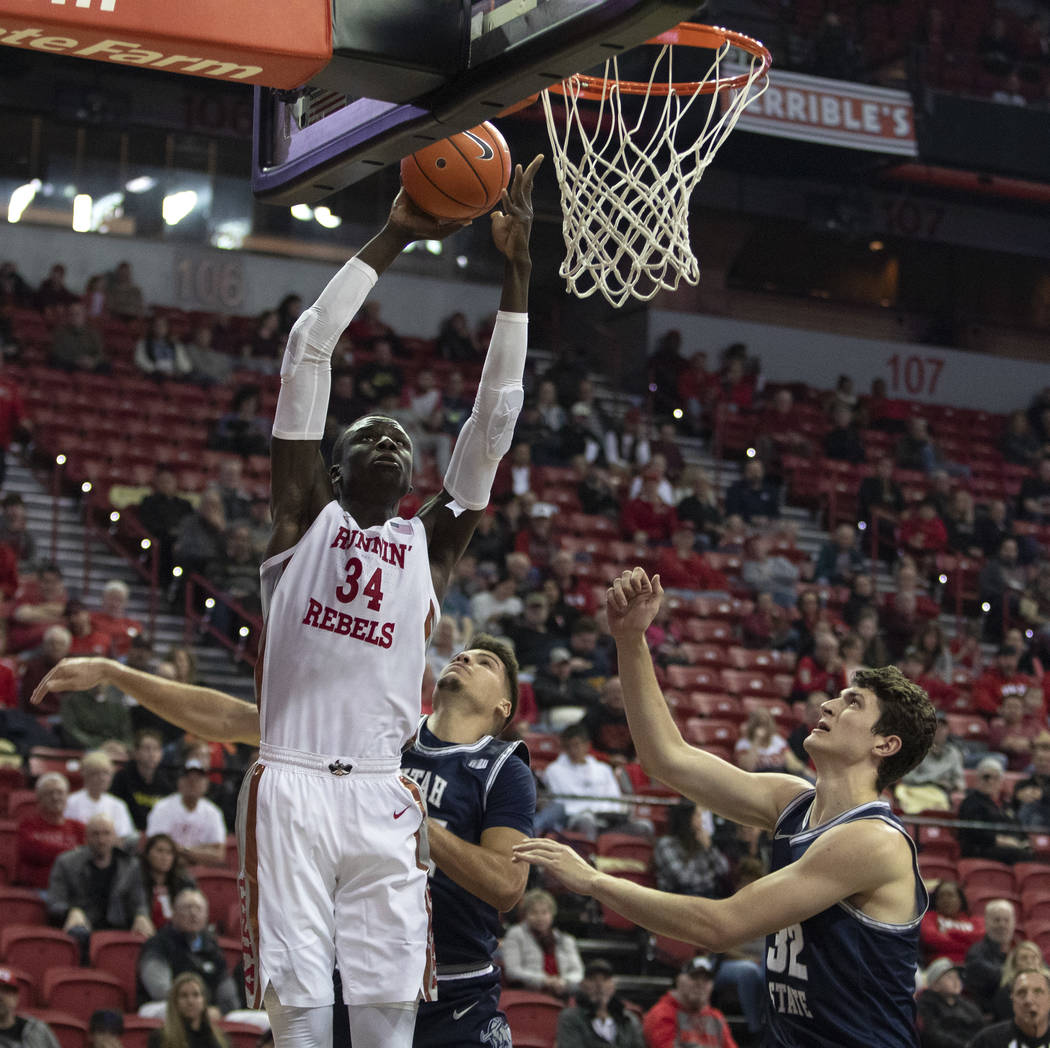 UNLV's forward Mbacke Diong shoots a point as Utah State's guard Diogo Brito (24) and center Tr ...