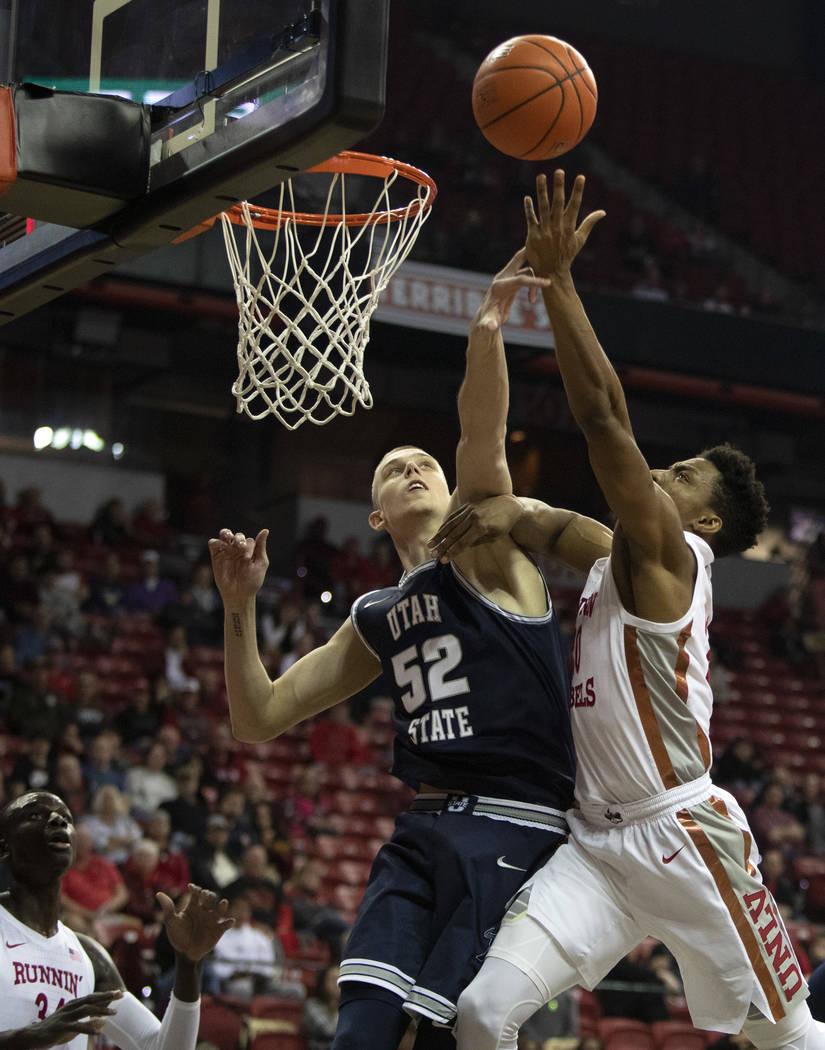 UNLV's forward Nick Blair (20) shoots a point as Utah State's center Kuba Karwowski (52) jumps ...