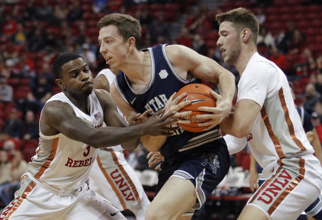 Utah State's Justin Bean, center, keeps the ball from UNLV's Amauri Hardy, left, and Vitaliy Sh ...