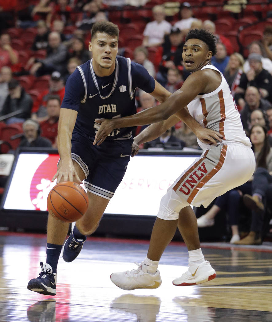 Utah State's Diogo Brito drives around UNLV's Bryce Hamilton during the first half of an NCAA c ...