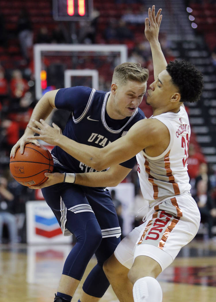 Utah State's Sam Merrill drives against UNLV's Marvin Coleman (31) during the first half of an ...