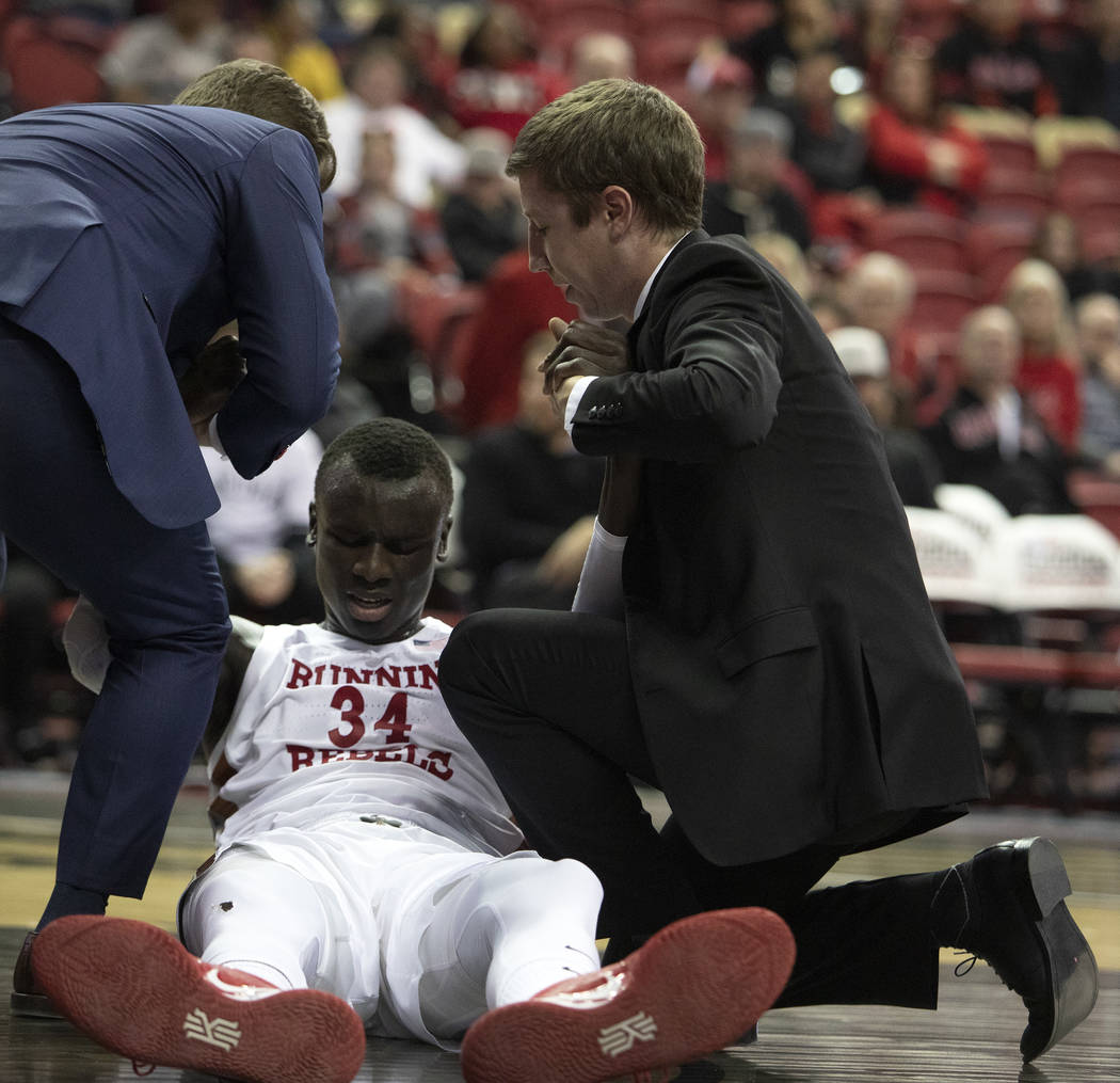 UNLV's forward Mbacke Diong (34) is pulled off the court by coaching staff during the first hal ...