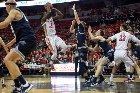 UNLV's guard Amauri Hardy (3) jumps to shoot a point as Utah State players reach to block him d ...