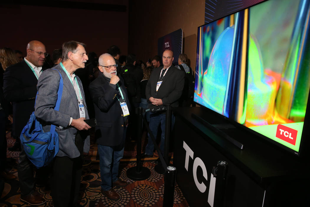 Members of the news media check out the TCL 8K Mini-LED TV during the TCL news conference at Ma ...