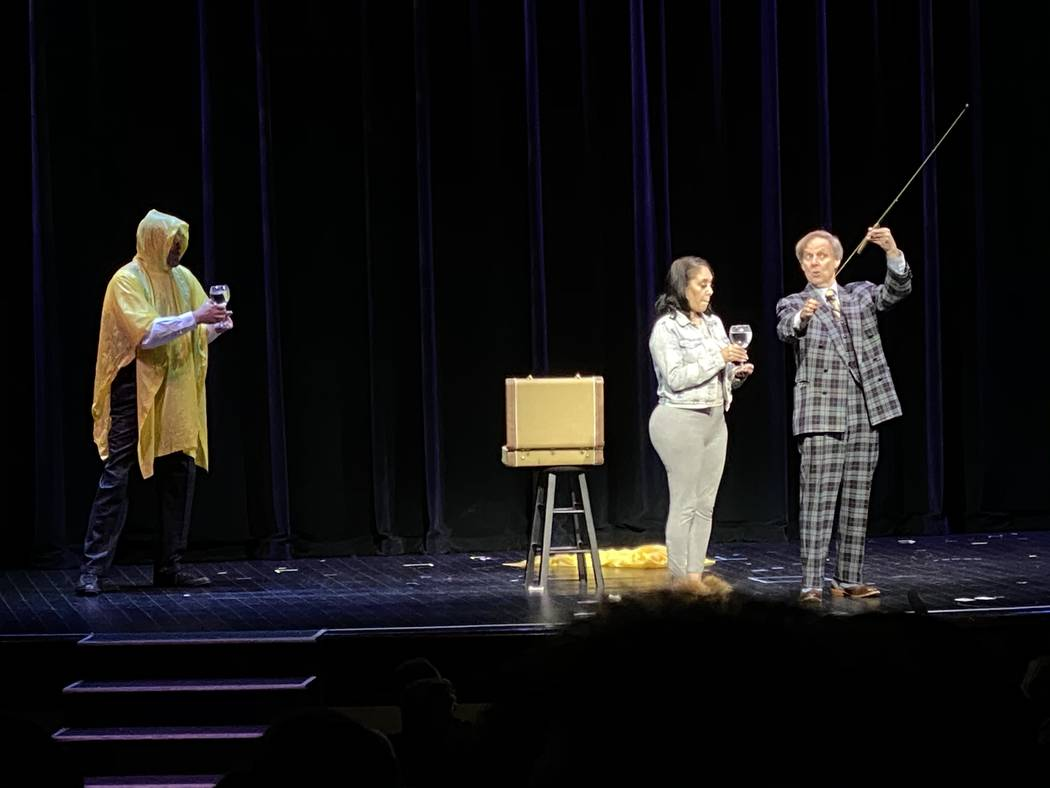 Penn Jillette, wearing the Cloak of Invisibility, and Mac King perform with an audience member ...
